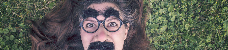 Frau mit Kunst-Bart und Brille
